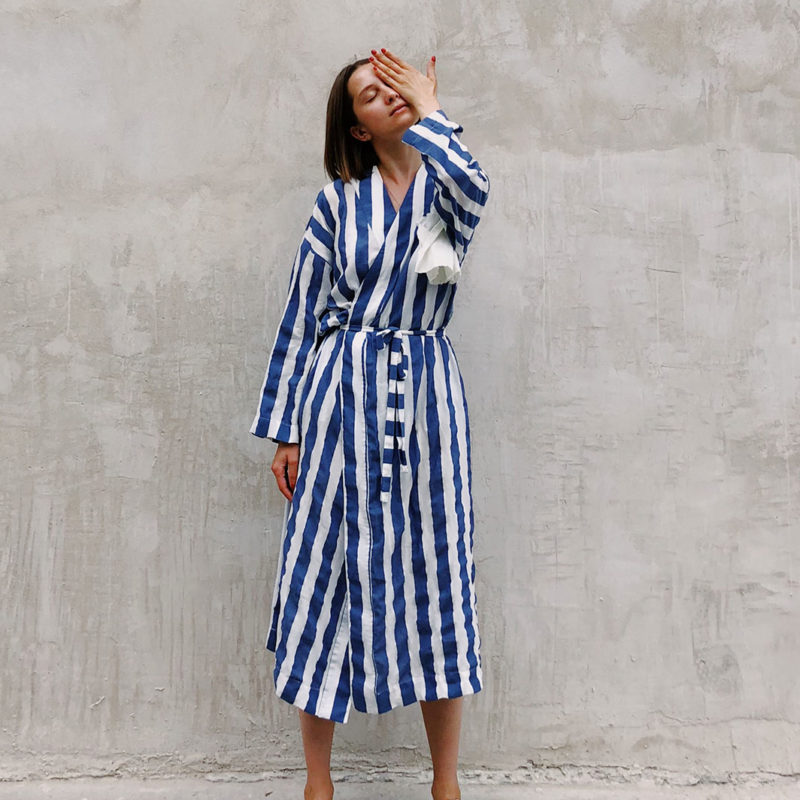 woman-in-blue-and-white-striped-dress-covering-her-left-eye-1182702
